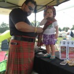 Getting dressed for the occassion! Jay Leask pins the weathered Leask tartan to his daughter Andromache.
